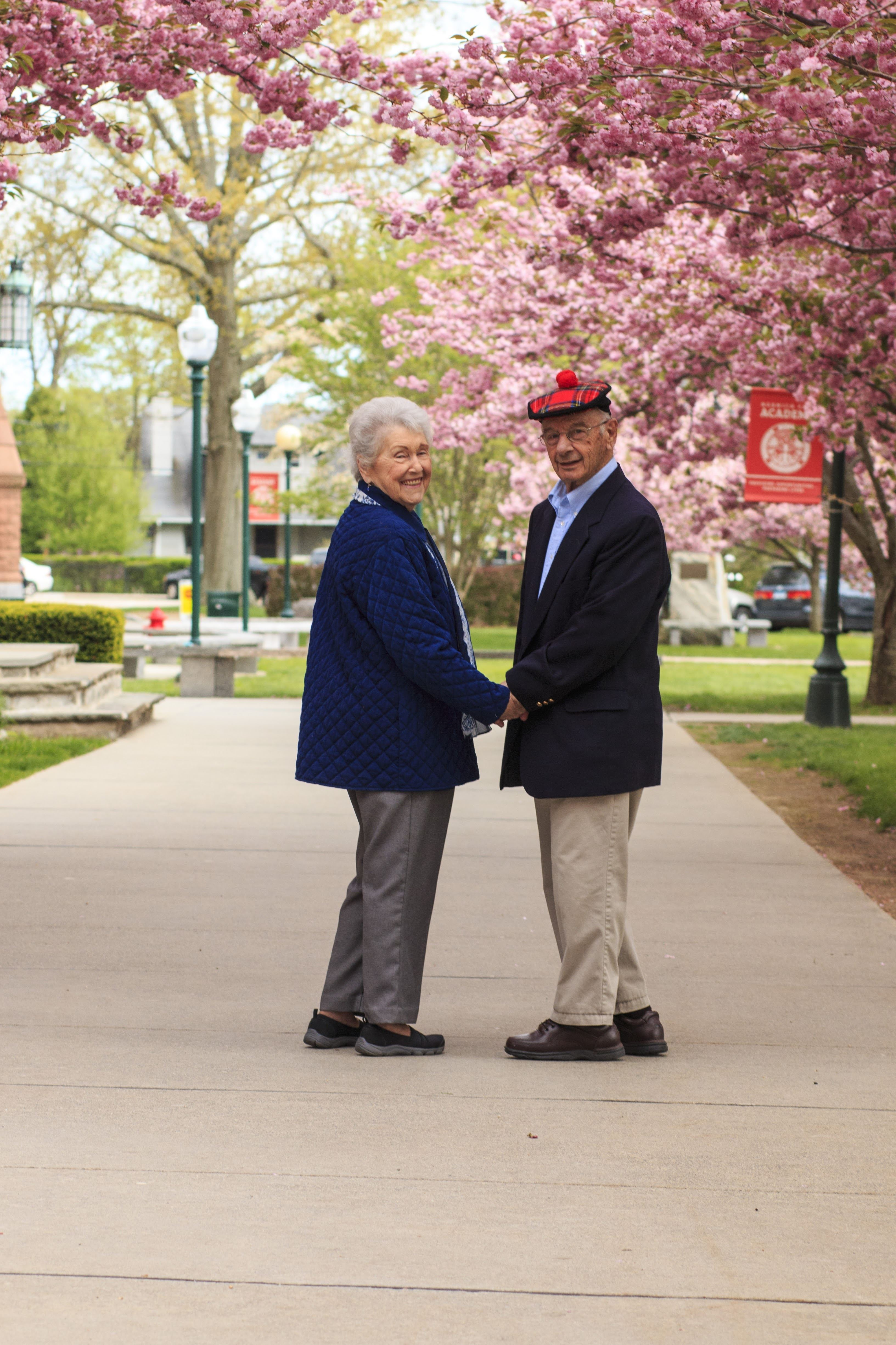 Don and Kitty Shaver Leone Class of 1968 standing under the blossoming cherry trees on the NFA Campus