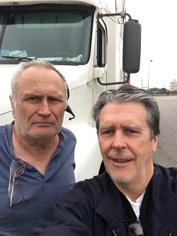 Rob Lenehan and Dennis Avery from the Class of 1963 standing in front of the cab of the truck Dennis drives.
