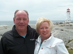 Kathy and a man standing on a rock formation with a lighthouse in the background