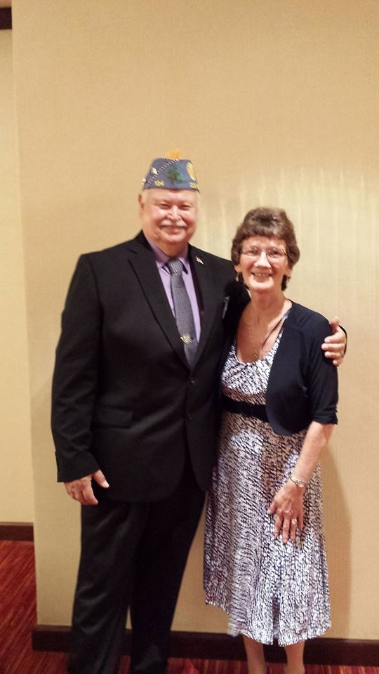 Richard Lurette Class of 1970 in a suit with his American Legion Commander hat posing with his wife Cecilia Craig Lurette Class of 1973