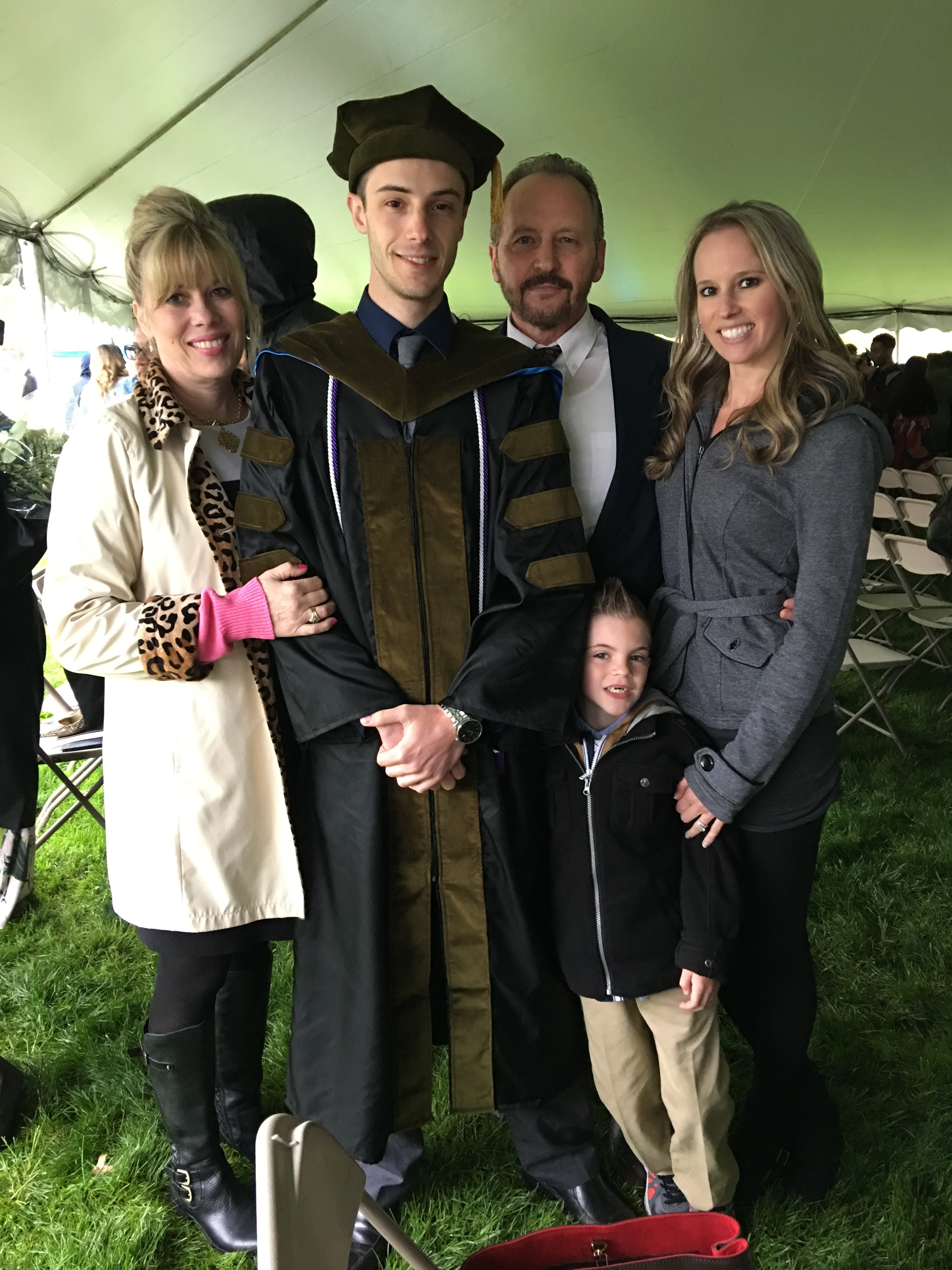 Stephanie Zema Bruneau Class of 1974 standing under an event tent with her son William when he received his Ph.D She is also with her husband, one of her daughters and one of her grandchildren.