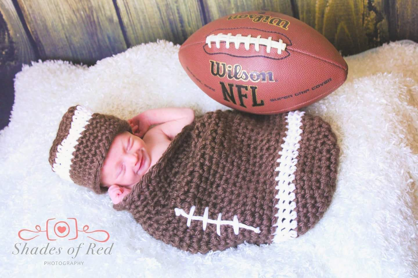 Alexander Joseph Fratoni, infant son of Bryan Fratoni Class of 2000, laying down nestled inside a crocheted football quilt with matching hat and a football next to him.