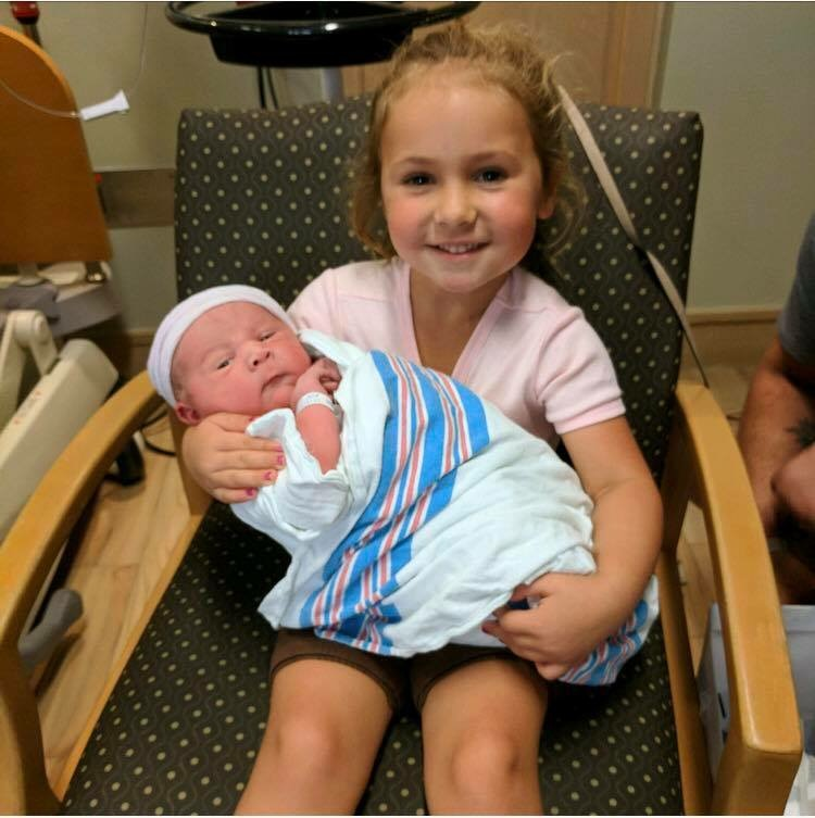 Five year old daughter Hazel holding her newborn brother Calvin