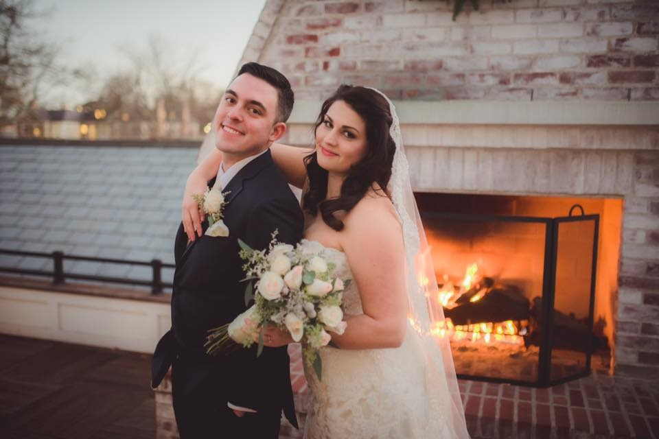 Lauryn Bonanno Class of 2007 and her husband Alan Brisson at their wedding posing in front of a fireplace.
