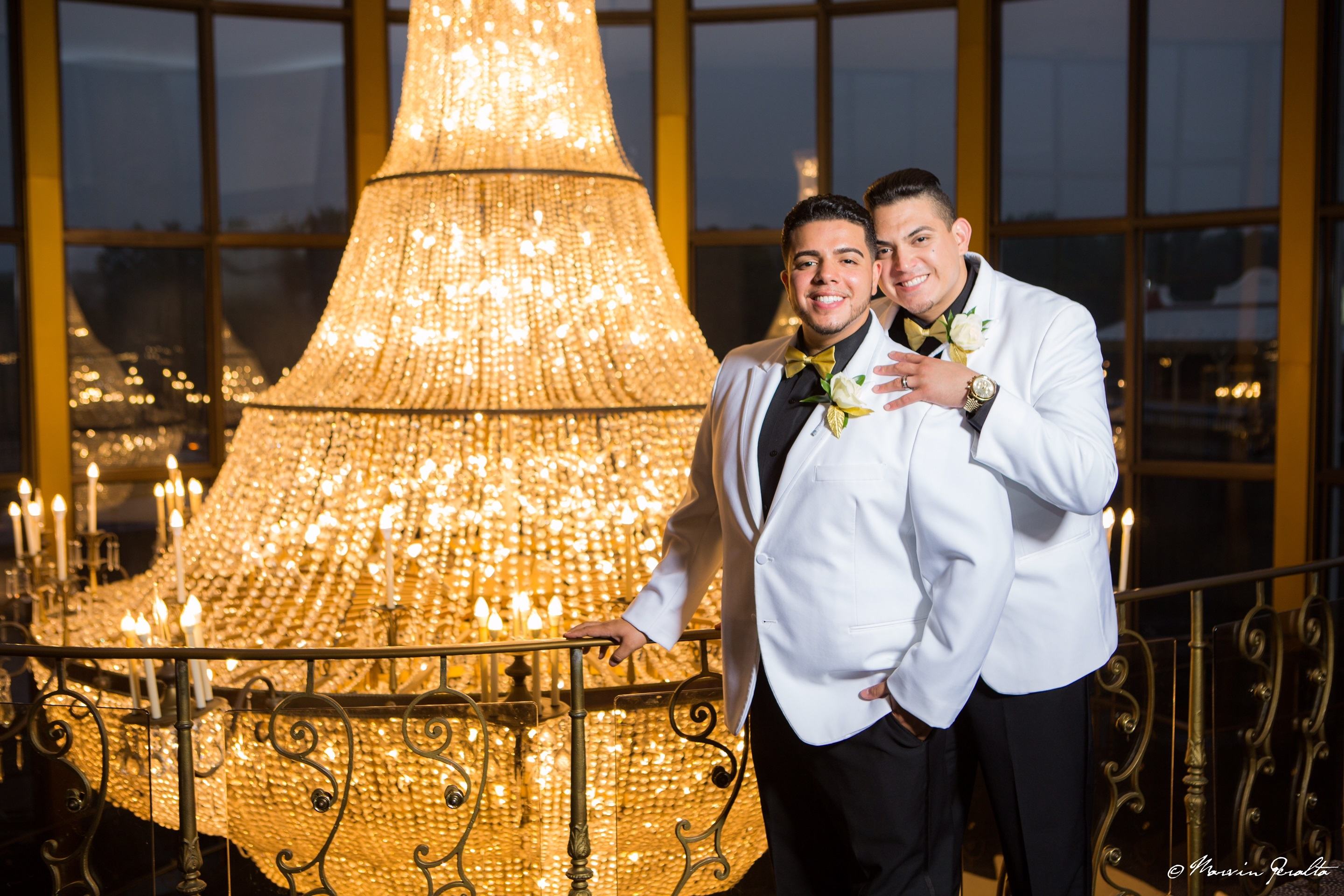 Jonathan Justiniano Ruiz Class of 2008 and his husband standing next to a large chandelier.