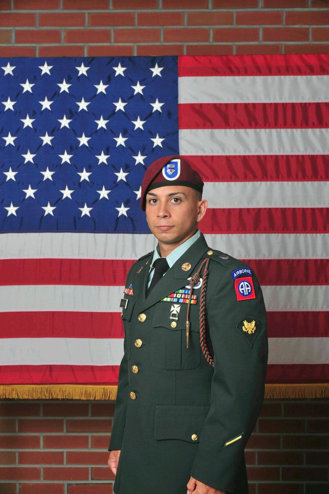 Andres Santiago Class of 2008 in his US Army Sergeants uniform standing in front of an American Flag