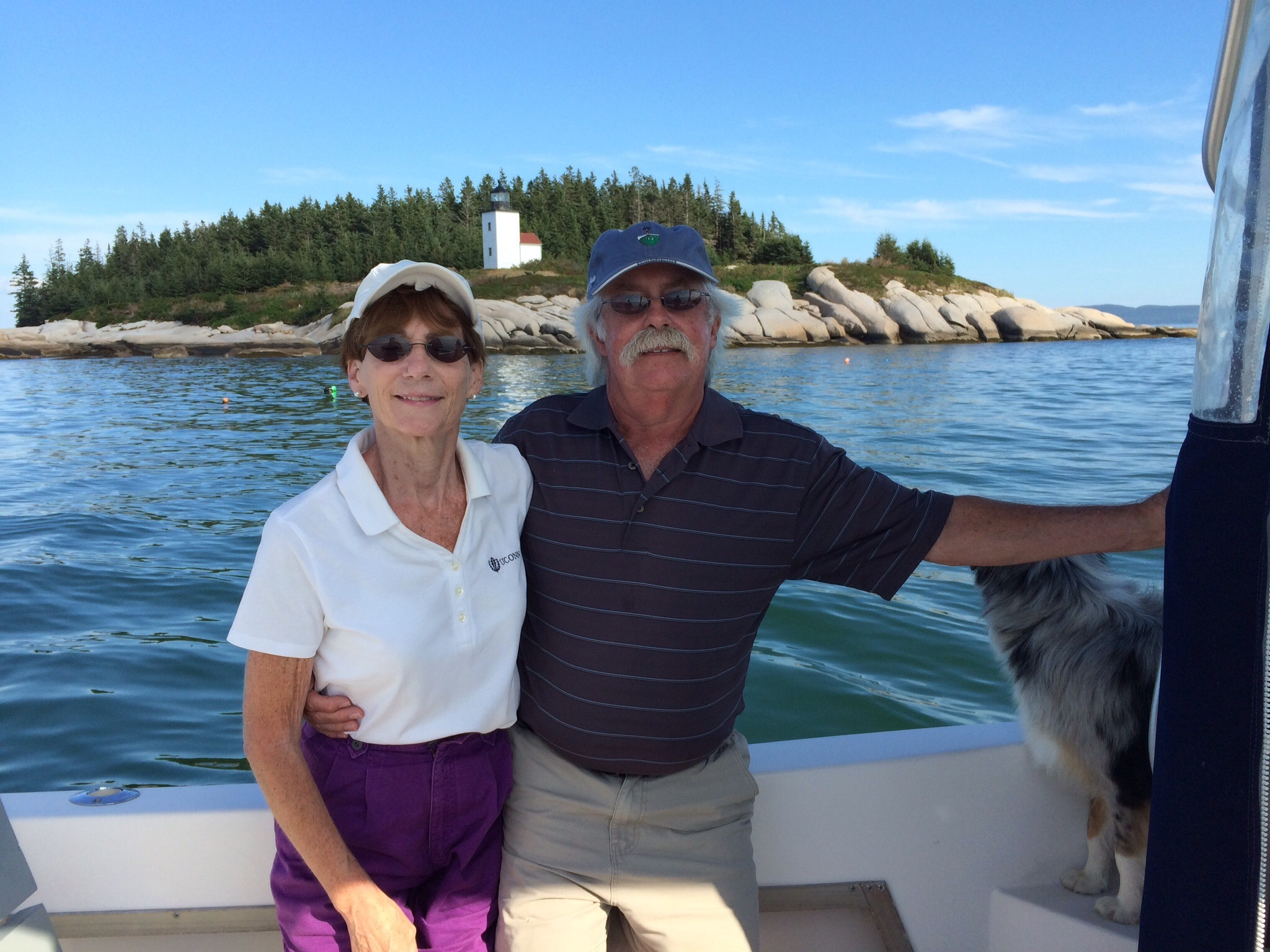 Ray Standish Class of 1965 with his wife Maureen on a boat in Maine with water and an island in the background
