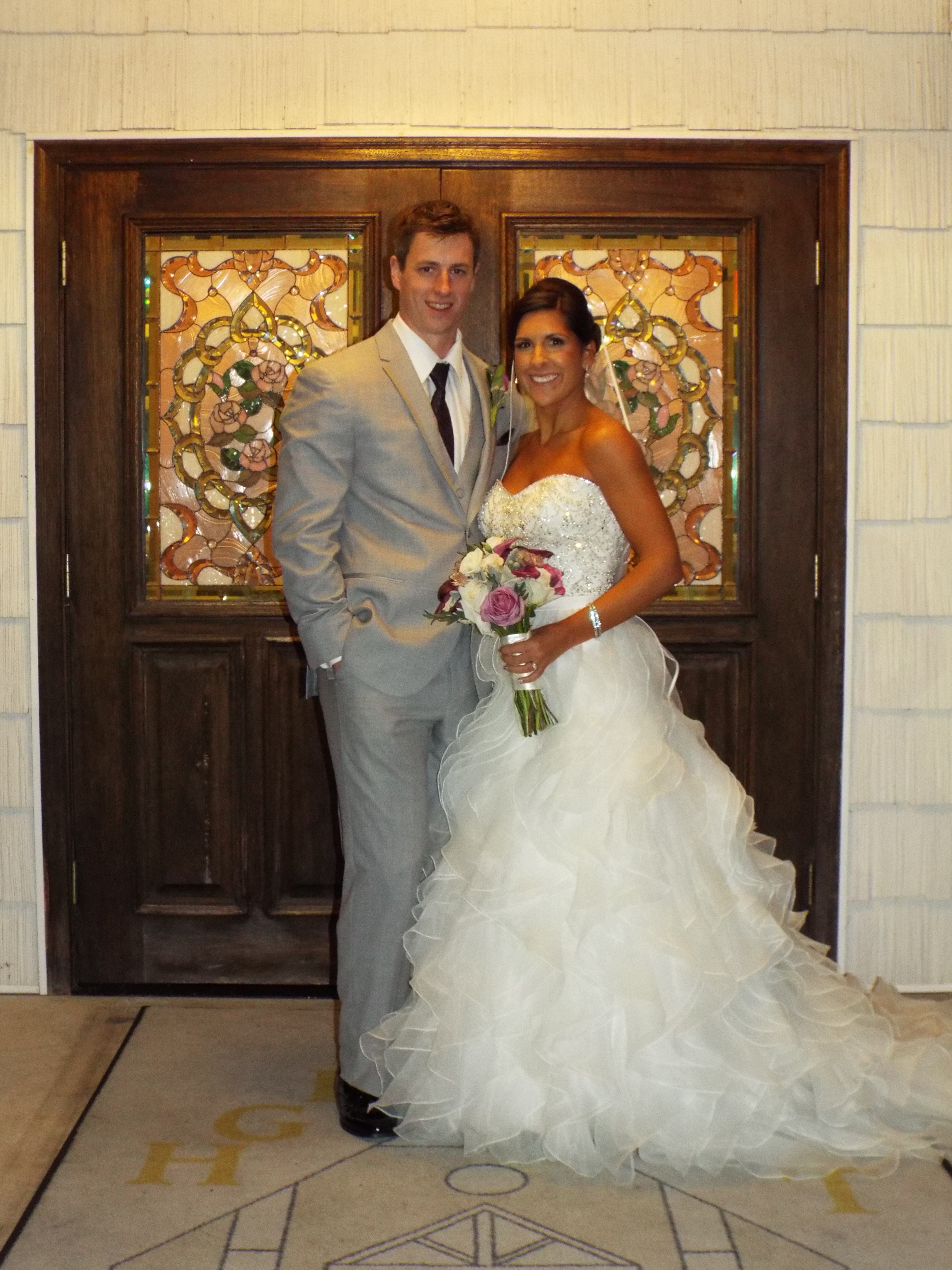 Ryan Guertin Class of 2007 and his bride Ashley Volpe on their wedding day standing in front of an ornate door